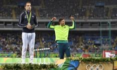 Thiago Braz recebe a medalha de ouro no Engenhão, ao lado de um abalado Lavillenie Foto: FABRICE COFFRINI / AFP