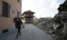 Bombeiro anda em meio a destruição em construções de Amatrice Foto: Antonio Calanni / AP