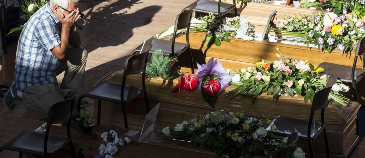 Um homem chora junto a um dos caixões alinhados em um ginásio da cidade de Ascoli Piceno, na região central da Itália, onde foi realizado funeral em massa de 35 vítimas do terremoto desta semana no país Foto: AP/Massimo Percossi
