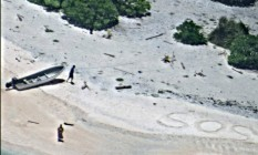 Perdidos. Na areia da desabitada Ilha de Fayu, na Micronésia, o pedido de socorro de um casal que foi encontrado por um avião da Marina americana Foto: AP