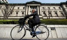 Um homem passa de bicicleta em frente à sede do Banco do Japão, em Tóquio Foto: Yuriko Nakao/Reuters/18-3-2009
