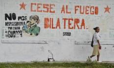 """Uma mulher passa por um mural em que se lê """"cessar-fogo bilateral"""" em uma rua de El Palo, no departamento de Cauca, na Colômbia Foto: LUIS ROBAYO / AFP"""