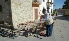 Um idoso limpa a rua na aldeia de Torrita, em Amatrice, poucos dias depois de um terremoto atingir a região Foto: ANDREAS SOLARO / AFP