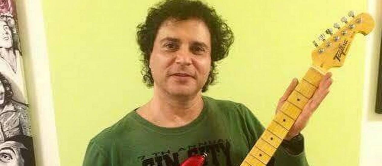 O roqueiro Roberto Frejat segura uma das duas guitarras doadas para serem leiloadas pela ONG Paraíso dos Focinhos Foto: Divulgação