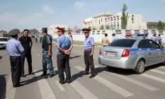 Investigadores e membros das forças de segurança se reúnem perto do local da explosão de uma bomba em frente à embaixada da China em Bishkek, no Quirguistão Foto: VLADIMIR PIROGOV / REUTERS