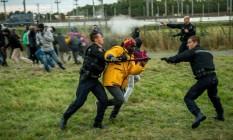 Em Coquelles, perto de Calais, policiais tentam impedir que imigrantes entrem no Eurotúnel para chegar ao Reino Unido Foto: Philippe Huguen/AFP