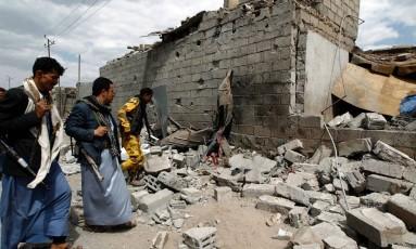 Iemenitas passam por pelo que restou de um prédio, em Sanaa Foto: MOHAMMED HUWAIS / AFP