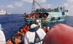 Funcionários da Guarda Costeira italiana resgatam migrantes na costa da Líbia Foto: HO / Guardia Costiera/AFP