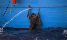 Imigrante se segura na beira de embarcação clandestina durante operação de resgate no Mediterrâneo Foto: Emilio Morenatti / AP