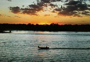 Bote a motor descendo o rio ao pôr do sol, numa imagem típica do Araguaia Foto: Eduardo Vessoni / Especial para O GLOBO