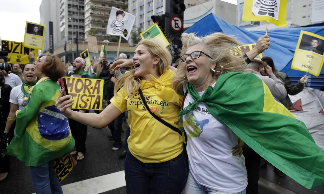 Manifestantes se abraçam e tiram fotos para comemorar Foto: Andre Penner / AP