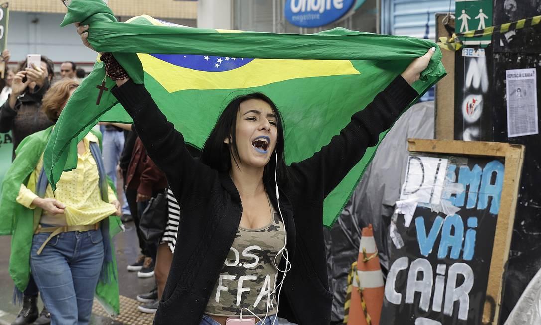 Militante pró-impeachment exibe bandeira do Brasil após o fim da decisão de depor a presidente Foto: Andre Penner / AP