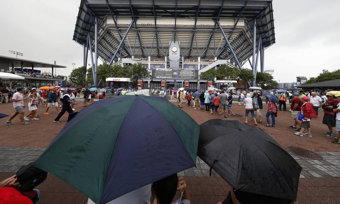 Espectadores se protegem da chuva em frente à Arthur Ashe, a quadra central do US Open Alex Brandon / AP