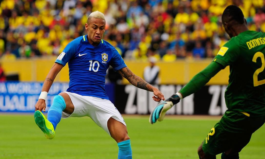 Neymar tenta bloquear o chute de Alexander Dominguez JUAN CEVALLOS / AFP