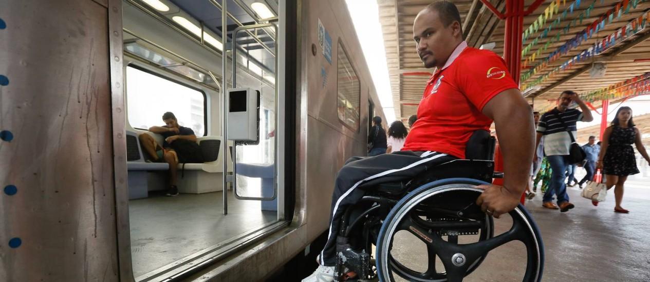 O cadeirante Claudecir Lopes recebeu ajuda de dois passageiros para conseguir superar o desnível entre o trem e a plataforma Foto: Pablo Jacob / Agência O Globo