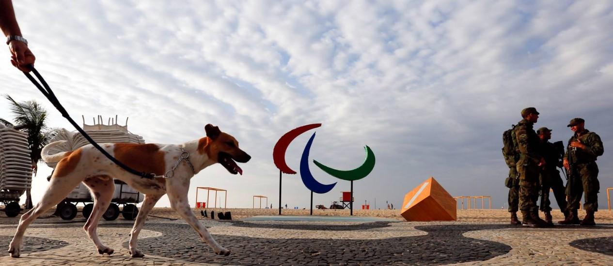 Homem passeia com cão enquanto soldados fazem segurança em Copacabana, perto do símbolo da Paralimpíada Foto: Carlos Garcia Rawlins / Reuter
