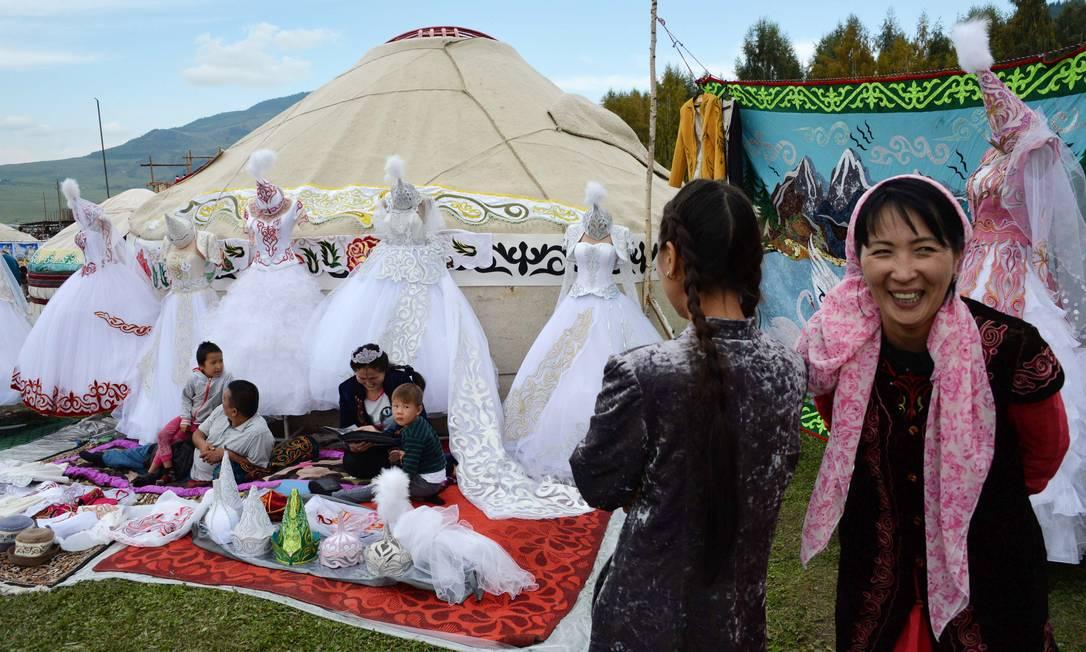 Mulheres exibem a cultura quirguiz, com artesanatos, roupas e comida em frente de yurtas (barracas de nômades) durante os Jogos Mundiais de Nômades de 2016, em Kyrchin, cerca de 300 kms da capital Bisqueque VYACHESLAV OSELEDKO / AFP