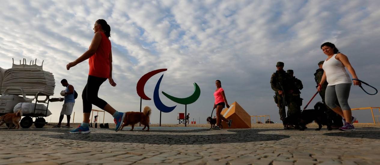 Pessoas passam em frente ao símbolo da Paralimpíada em Copacabana Foto: Carlos Garcia Rawlins / Reuters