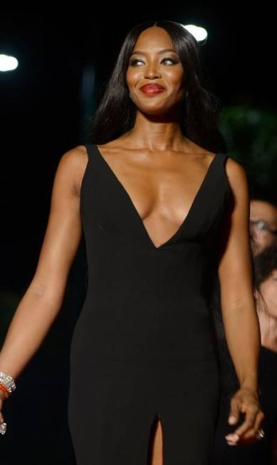 Em suas últimas aparições públicas, Noami Campbell vem apostando em produções mais ousadas. No Festival de Veneza, apostou no combo fenda + decote, ao lado de Donatella Versace. FILIPPO MONTEFORTE / AFP
