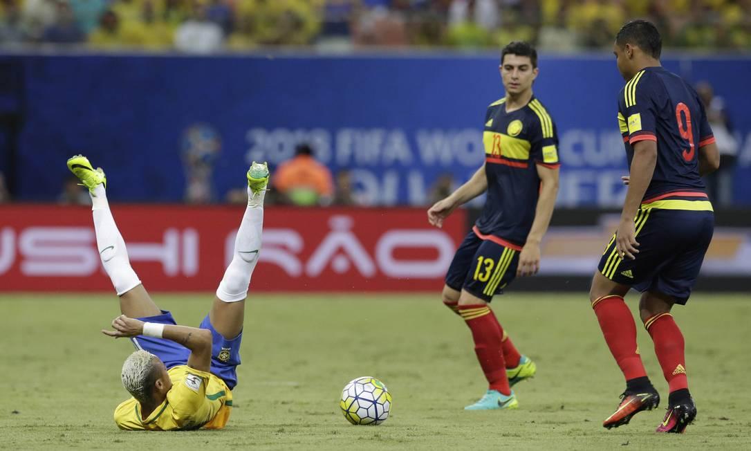Neymar cai sentado durante disputa de bola com a marcação colombiana Leo Correa / AP