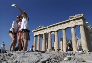 Turistas em frente ao Parthenon, em Atenas. A capital grega é um dos exemplos de destinos com passagens mais baratas em 2016 Foto: Christian Hartmann / Reuters