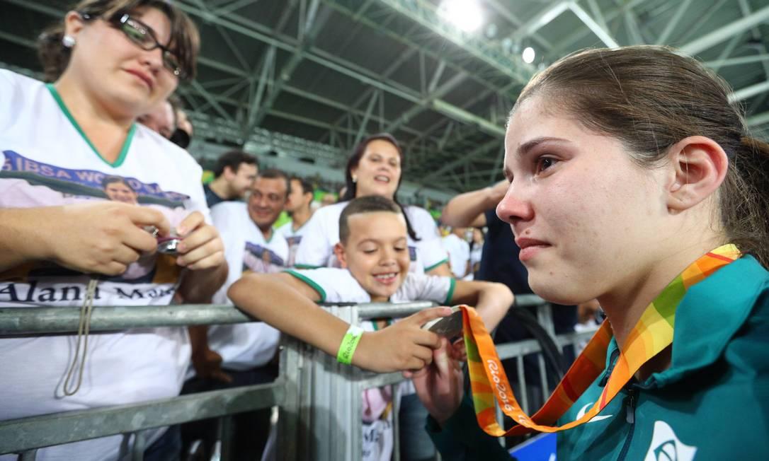 O garotinho admira de pertinho a medalha de prata conquistada por Alana Maldonado na categoria até 70 kg do judô (B2, atletas com percepção de vultos) Pablo Jacob / Agência O Globo