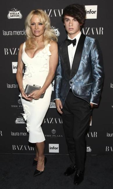 """Aos 49 anos e decotada, Pamela Anderson virou a sensação da semana de moda de Nova York. Ela anda circulando pelos desfiles e festinhas com Dylan Jagger Lee, seu filho de 18 anos com Tommy Lee. Na foto, a dupla fashion no evento da revista americana """"Harper's Bazaar"""" Andy Kropa / Andy Kropa/Invision/AP"""