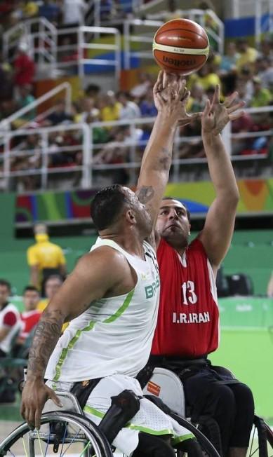 A disputa da bola é lá no alto, e o brasileiro e o iraniano se esticam na cadeira para superar o adversário Monica Imbuzeiro / Agência O Globo