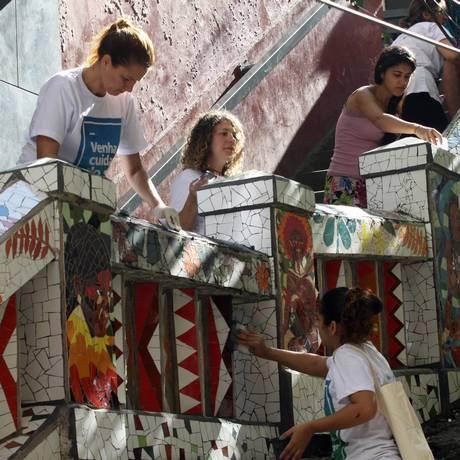 Moradores colam os mosaicos na escadaria que dá acesso ao morro: obra foi sugerida pela comunidade Foto: Paulo Nicolella / Agência O Globo