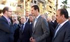 Imagem divulgada pela agência Sana mostra o presidente sírio, Bashar al-Assad (centro), falando com a imprensa após ir a uma mesquita em Daraya Foto: HO / AFP