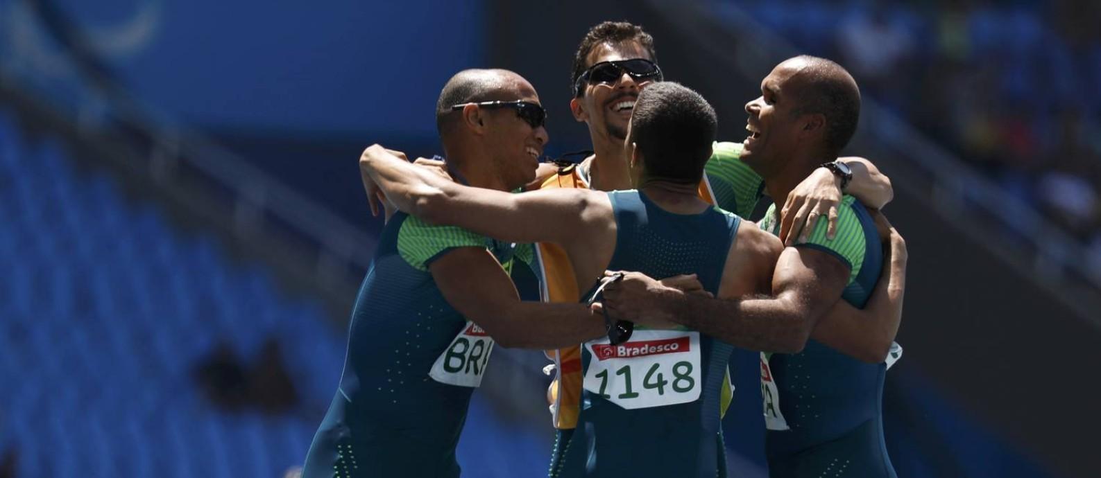 Um dos dois guias e três dos quatro corredores da equipe brasileira de revezamento festejam o ouro no 4x100m da classe T11-13 Foto: RICARDO MORAES / REUTERS