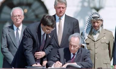 Em 13 de setembro de 1993, Peres (então chanceler israelense) assina os históricos acordos de paz na Casa Branca para dar autonomia aos palestinos nos territórios ocupados. É visto, ao fundo, por seu premier, Yitzhak Rabin, pelo presidente americano, Bill Clinton (centro) e pelo líder palestino, Yasser Arafat Foto: J. DAVID AKE / AFP