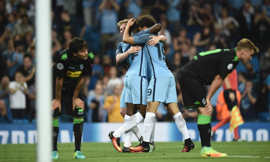 Kelechi Iheanacho, atacante do Manchester City, recebe os abraços de companheiros de time na goleada por 4 a 0 sobre o Borussia Monchengladbach OLI SCARFF / AFP