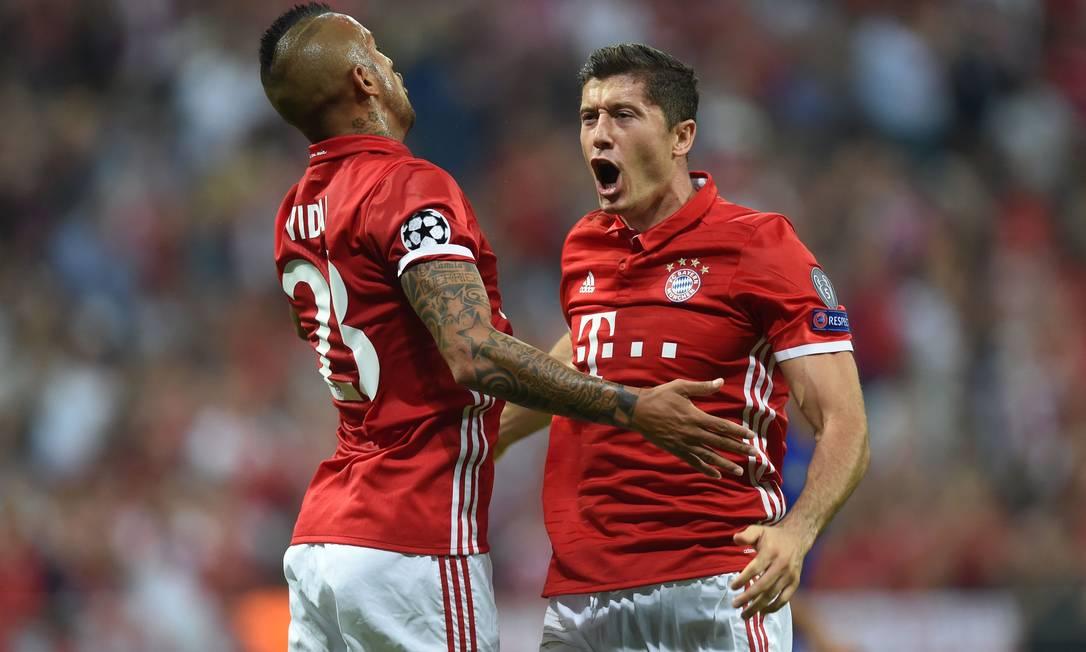 Toda a euforia de Vidal (à esquerda) e Lewandowski na goleada do Bayern de Munique sobre o Rostov, da Rússia, por 5 a 0 CHRISTOF STACHE / AFP