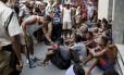 Observados por guardas municipais e uma multidão de curiosos, jovens que provocaram tumulto em Copacabana aguardam, sentados na calçada, a ida para uma delegacia: pelo menos 110 passaram por averiguação