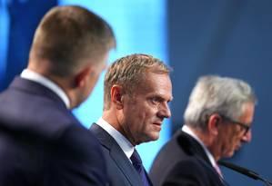 Permier eslovaco, Robert Fico (esquerda), Donald Tusk (centro) e Juncker dão coletiva de imprensa: reunião teve promessas, mas poucos consensos Foto: YVES HERMAN / REUTERS