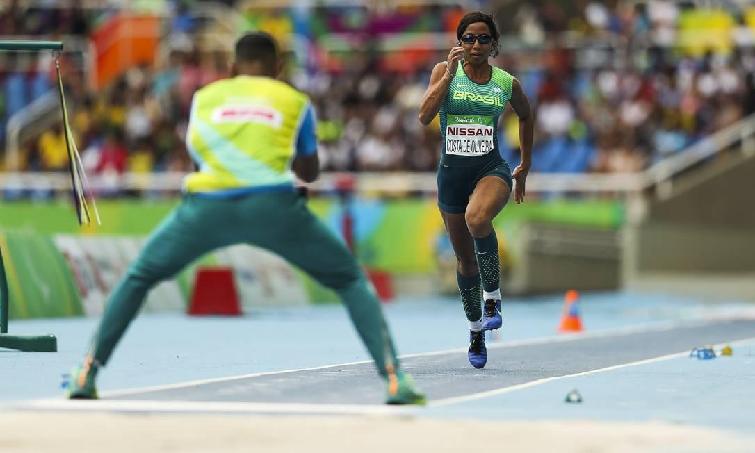 Orientada pelo guia, Silvânia corre para saltar e conquistar o ouro na prova do salto em distância, classe T11 Foto: Guilherme Leporace / Agência O Globo