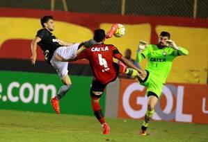 Rodrigo Pimpão se estica e bate na bola, entre o zagueiro Ramon e o goleiro Fernando Miguel, do Vitória, para marcar o gol do Botafogo em Salvador: 1 a 0 Foto: Edson Ruiz / Coofiav / Agência O Globo