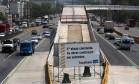 Placa na Avenida Brasil informa que as obras do BRT seriam retomadas este mês, mas os canteiros estão vazios Foto: Custódio Coimbra / Agência O Globo