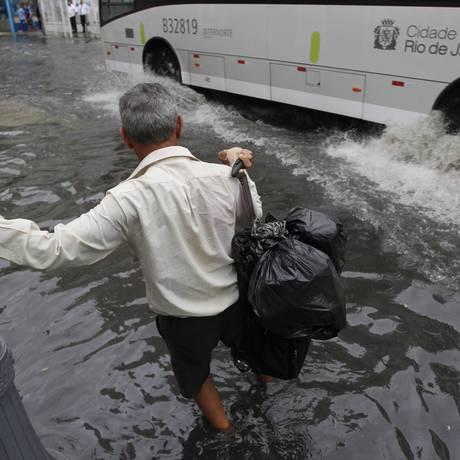 Homem tenta passar pela Rua da Lapa alagada Foto: Pedro Teixeira / Agência O Globo