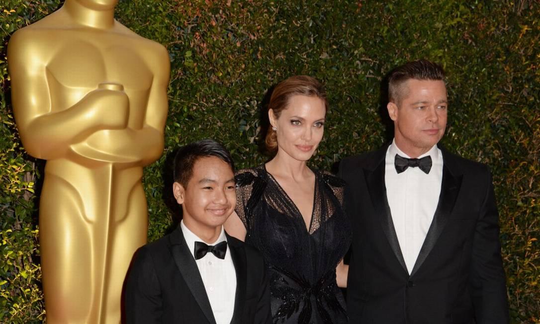 Aqui, Angelina e Brad posam com Maddox Jolie-Pitt no Governors Awards de 2013. Hoje, o menino tem 15 anos e é irmão de Vivienne (8 anos), Knox Leon (8), Shiloh (10 anos), Zahara (11 anos) e Pax Thien (12) ROBYN BECK / AFP