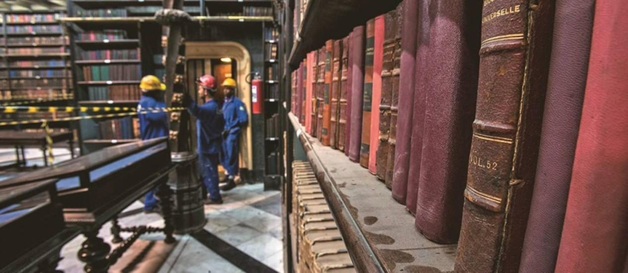 Operários trabalham na limpeza dos livros após a conclusão da reforma do telhado: o Real Gabinete alega que nenhum volume do acervo foi danificado Foto: Alexandre Cassiano