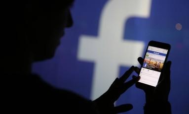 Mulher checa site do Facebook em seu celular Foto: Bloomberg