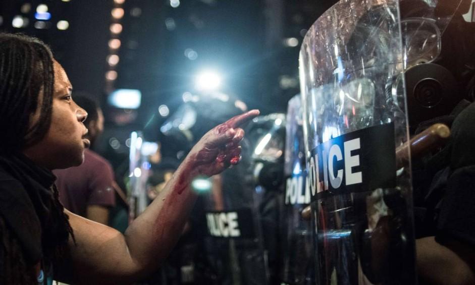 Uma mulher com sangue nas mãos aponta para policial em Charlotte, na Carolina do Norte. Manifestantes protestam contra a morte de Keith Scott, um homem negro de 43 anos assassinado por policiais Foto: Sean Rayford / AFP
