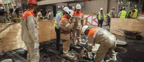 Técnicos da Light vistoriam instalações junto ao bueiro da CEG. Pedestres que passavam pelo Centro se assustaram com explosões Foto: Hermes de Paula