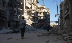 Homem sírio caminha por área pesadamente danificada de Aleppo após os intensos bombardeios de forças do governo contra posições de rebeldes no Leste da cidade, que danificaram estação de abastecimento Foto: AFP/KARAM AL-MASRI