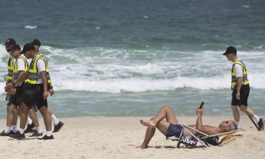 Policiais em grupo ou duplas circulam pelas areias do Arpoador. Foto: Ana Branco / Agência O Globo