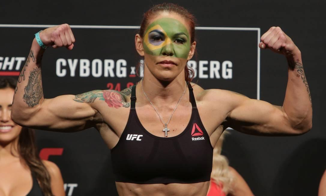 Invicta desde 2005, e pela segunda vez no UFC, Cris Cyborg se enfeita com as cores da bandeira brasileira na pesagem: sintonia total com a torcida Eraldo Peres / AP