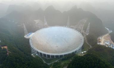 O radiotelescópio chinês FAST, com sua antena de 500 metros de diâmetro, em meio à névoa na montanhosa no Sudoeste da província de Guizhou no seu primeiro dia de funcionamento Foto: STR / AFP