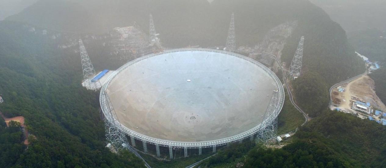 O radiotelescópio chinês FAST, com sua antena de 500 metros de diâmetro, em meio à névoa na montanhosa no Sudoeste da província de Guizhou no seu primeiro dia de funcionamento Foto: AFP